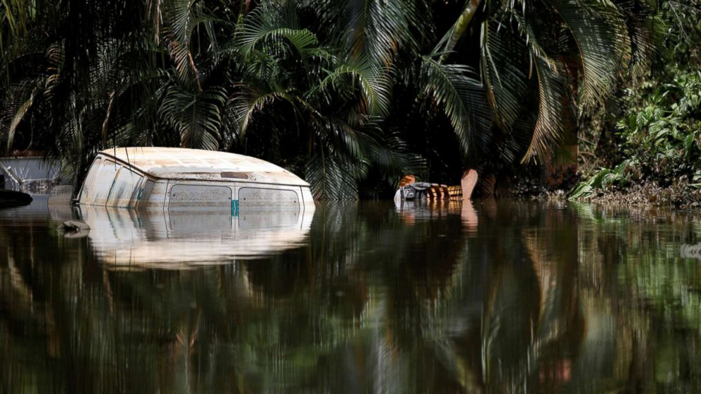 A car submerged in flood waters is seen close to the dam of the Guajataca lake after the area was hit by Hurricane Maria in Guajataca, Puerto Rico, Sept. 23, 2017.