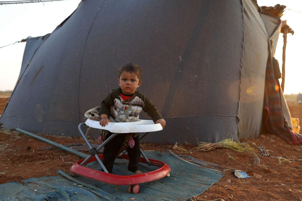 A Syrian infant is seen in a baby walker outside a tent at a camp for displaced civilians fleeing from advancing government forces near the village of Sarman in the rebel-held northwestern Idlib province, Sept. 1, 2018.