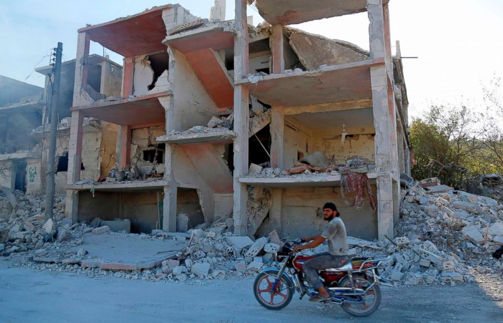 PHOTO: A Syrian man rides a motorcycle past a destroyed building in an area that was hit by a reported air strike in the district of Jisr al-Shughur, in the Idlib province, on Sept. 4, 2018.