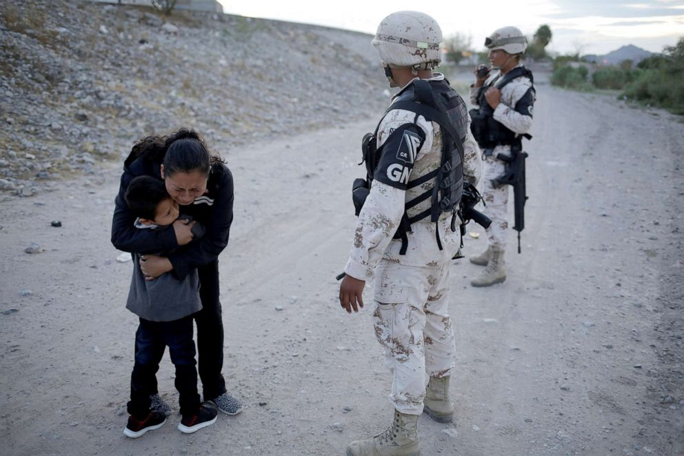 PHOTO: Guatemalan migrant Lety Perez embraces her son Anthony while asking to members of the Mexican National Guard to let them cross into the United States, as seen from Ciudad Juarez, Mexico July 22, 2019