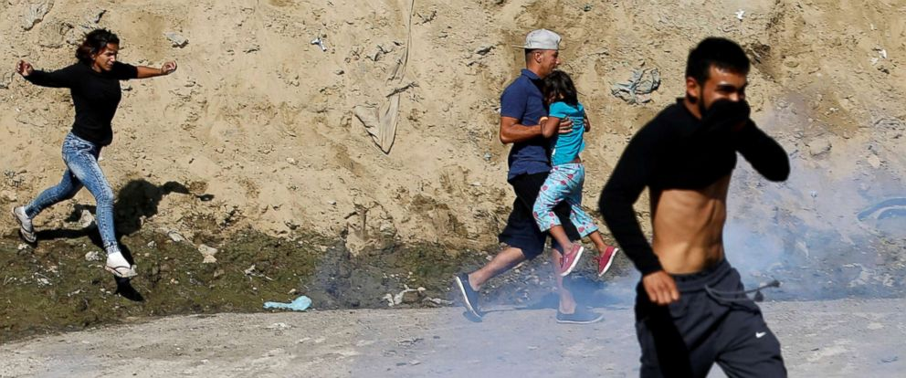 PHOTO: Migrants, part of a caravan of thousands traveling from Central America en route to the United States, run from tear gas released by U.S. border patrol near the fence between Mexico and the United States in Tijuana, Mexico, Nov. 25, 2018.