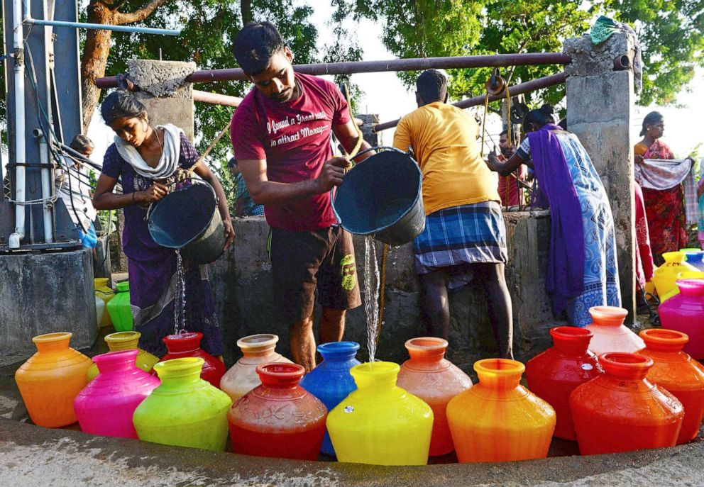 PHOTO: In this photo taken on June 20, 2019, Indian residents pour water into pots after fetching from a community well in Chennai after reservoirs for the city ran dry.