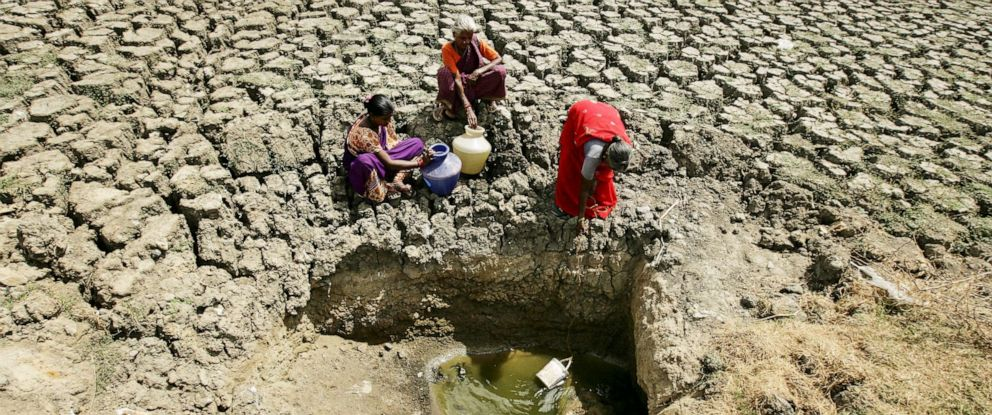 PHOTO: Women fetch water from an opening made by residents at a dried-up lake in Chennai, India, June 11, 2019.