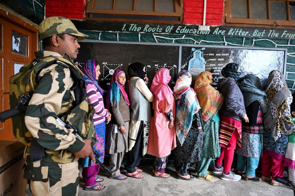 PHOTO: Kashmiri Muslim voters stand in a queue an as Indian Border Security soldier walks past at a polling station during the first phase of Indias general election in Handwara, north of Srinagar, April 11, 2019.