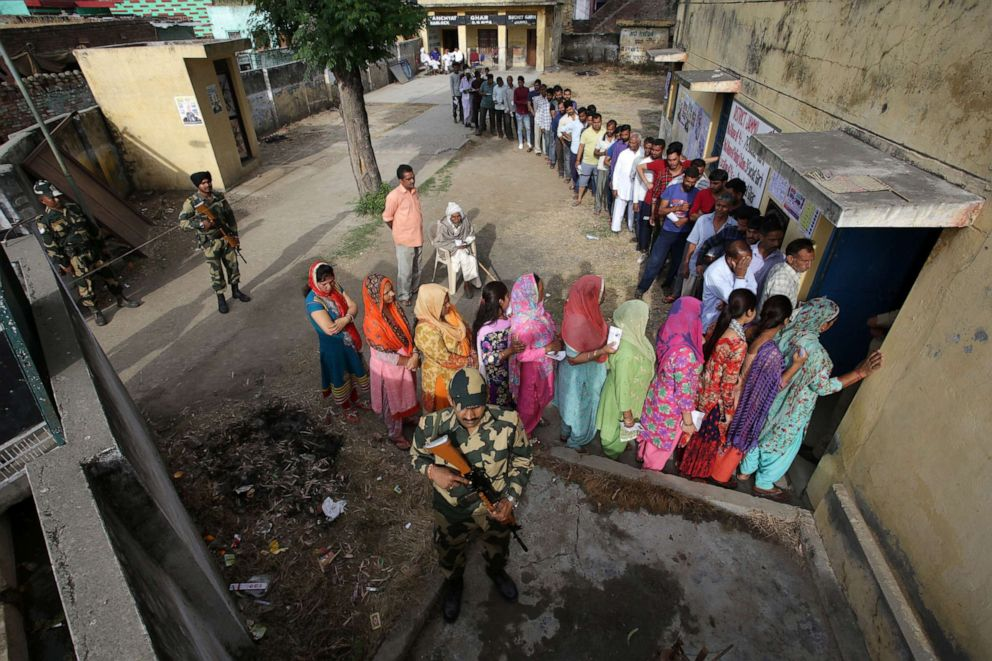 PHOTO: Indian Border Security Force soldiers stand guard as villagers queue up to cast their votes at a polling station near the India-Pakistan international border, India, April 11, 2019.