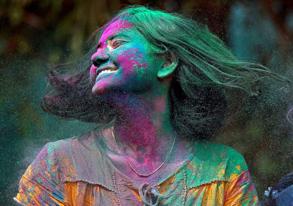 PHOTO: The tradition of throwing colored powder and water is believed to originate from the mythological love story of Radha and Krishna. A woman smeared with colored powder shakes her head during Holi celebrations in Mumbai, India on March 2, 2018.