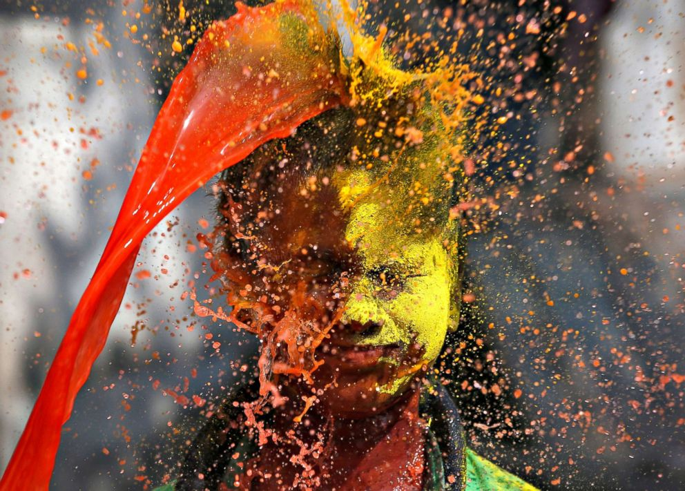 PHOTO: Colored water is poured on a boy during Holi celebrations in Kolkata, India on March 2, 2018.