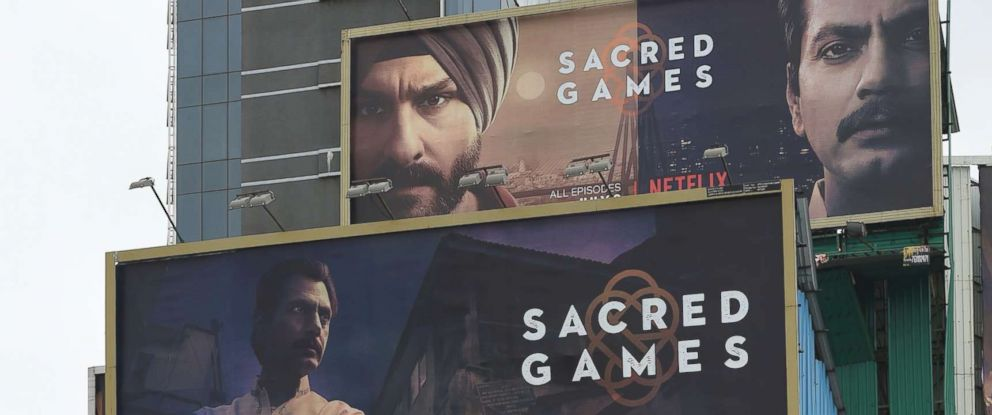 "PHOTO: Indian commuters travel past large billboards for ""Sacred Games"", the upcoming Indian series on Netflix, in Mumbai in this July 4, 2018 file photo."