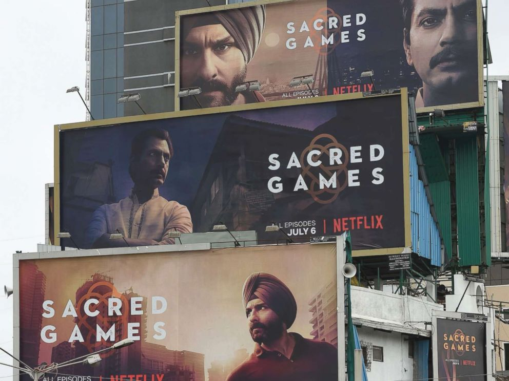 PHOTO: Indian commuters travel past large billboards for Sacred Games, the upcoming Indian series on Netflix, in Mumbai in this July 4, 2018 file photo.