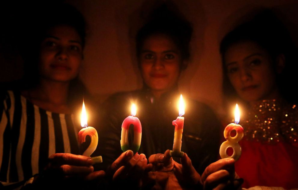 PHOTO: Indian girls pose for photographs with lighted candles during celebrations to welcome the new year in Bhopal, India, Dec. 31, 2017.