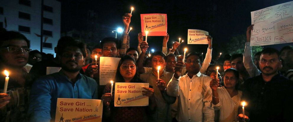 PHOTO: People hold candles and placards during a vigil as they protest against the rapes in Ahmedabad, India, April 15, 2018.