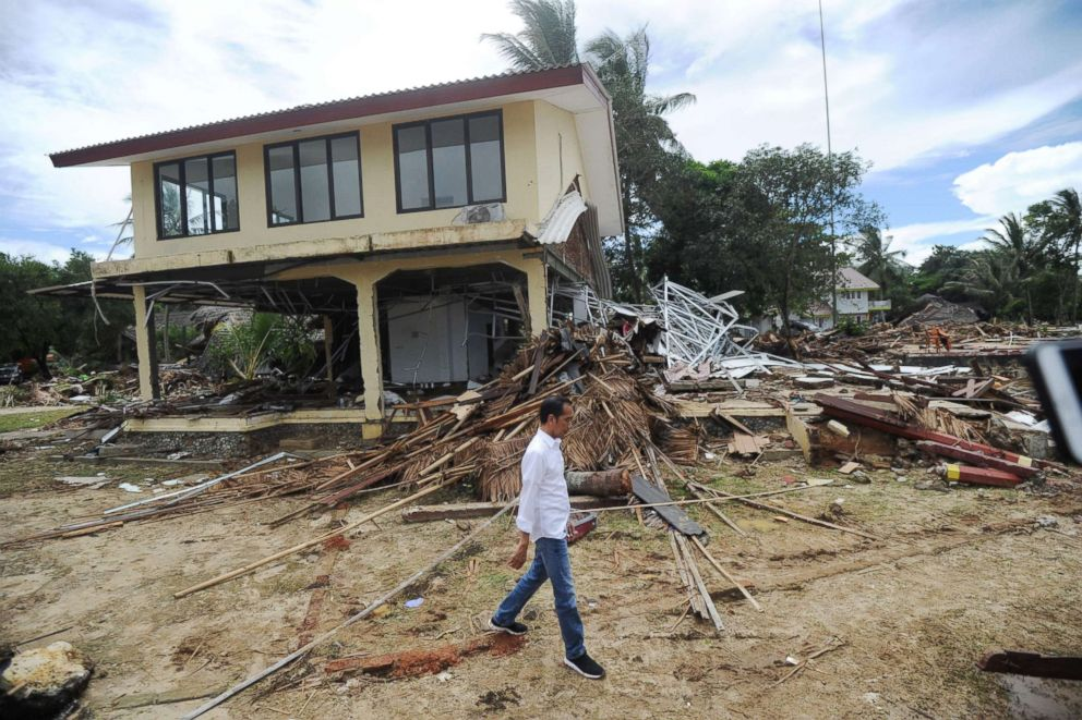 PHOTO: Indonesias President Joko Widodo walks past debris at the Mutiara Carita Cottages in Carita in Banten province on Dec. 24, 2018, two days after a tsunami.