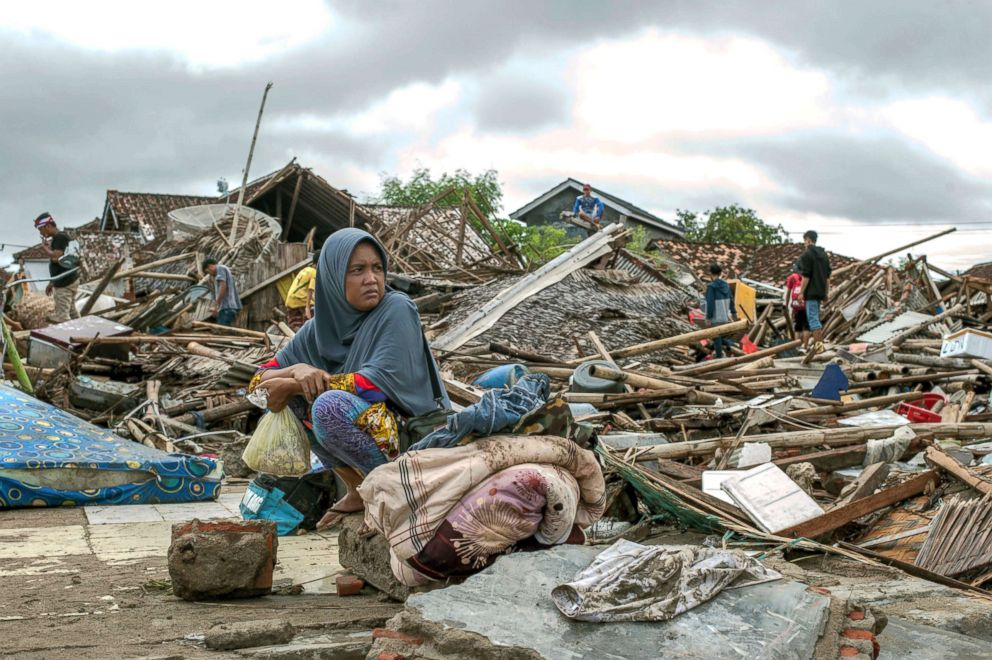 PHOTO: A tsunami survivor sits on a piece of debris as she salvages items from the location of her house in Sumur, Indonesia, Dec. 24, 2018.