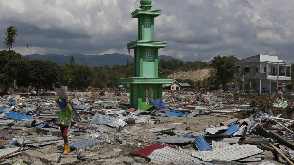 A man carries recovered items from the damaged warehouse from Friday's tsunami at a neighborhood in Donggala, Central Sulawesi, Indonesia, Tuesday, Oct. 2, 2018.