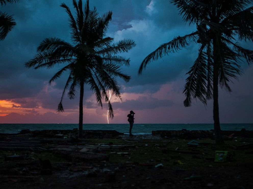PHOTO: A photojournalist is silhouetted by the sunset as a lightning strike at a resort affected by Saturdays tsunami in Carita, Indonesia, Tuesday, Dec. 25, 2018.