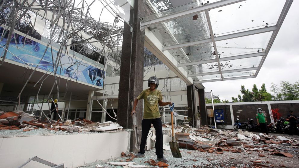 A man cleans up at a building damaged by an earthquake in Bali, Indonesia, Monday, Aug. 6, 2018.