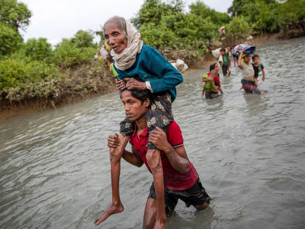 PHOTO:A Rohingya Muslim man carries an elderly woman through water after crossing the border from Myanmar into Bangladesh, near Palong Khali, Nov. 1, 2017.