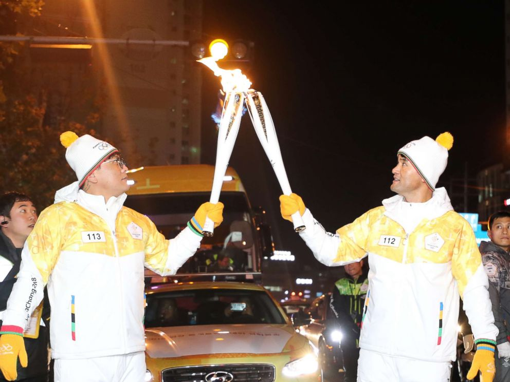 PHOTO: Retired major league pitcher Park Chan-ho, right, delivers the Olympic flame for the 2018 PyeongChang Games to Hanwha Eagles slugger Kim Tae-gyun at an event in Daejeon on Dec. 9, 2017, as part of the Olympic torch relay.
