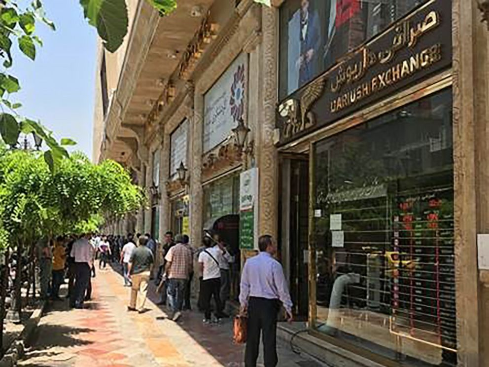 PHOTO: People look at currency deals on the sidewalk of Ferdowsi Street in Tehran, Iran, days after the visit of Japans Prime Minister, Shinzo Abe, June 15, 2019.