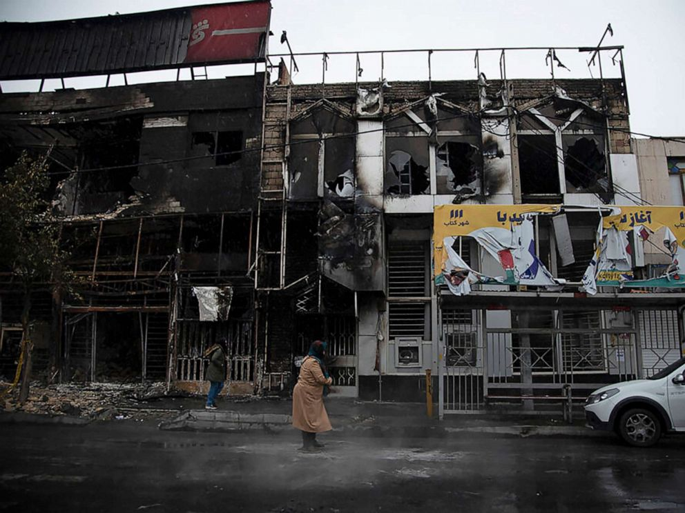 PHOTO: People walk past buildings which burned during protests that followed the rise of gasoline prices, in the city of Karaj, west of Tehran, Iran, Nov. 18, 2019, in a photo released by Iranian Students News Agency, ISNA.