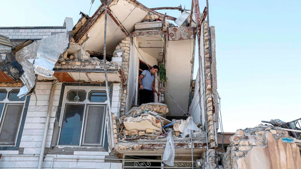 An Iranian man looks through the damaged stairwell of a building in the town of Sarpol-e Zahab in the western Kermanshah province near the border with Iraq, Nov. 14, 2017, following a 7.3-magnitude earthquake that left hundreds killed and thousands homeless two days before.
