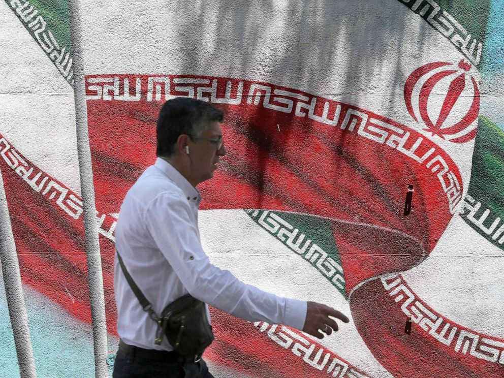 PHOTO: An Iranian man walks past a mural painted with the Iranian flag in Tehran on June 25, 2019.