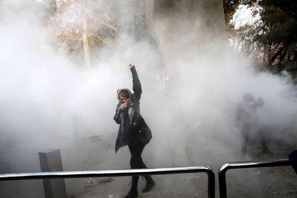 A university student attends a protest inside Tehran University as a smoke grenade is thrown by anti-riot Iranian police, in Tehran, Iran, Dec. 30, 2017, in a photo obtained by the AP.