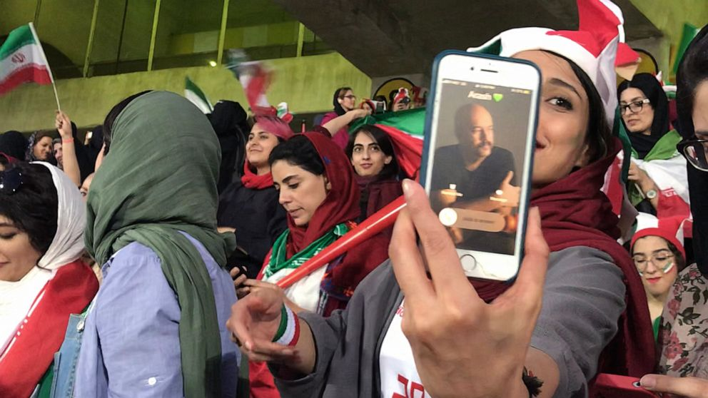 PHOTO: Zahra Ahooei receives a phone call from her husband during half time while attending a soccer game in Tehran, Iran, Oct. 10, 2019. They could not sit besides each other because men and women sections are segregated.