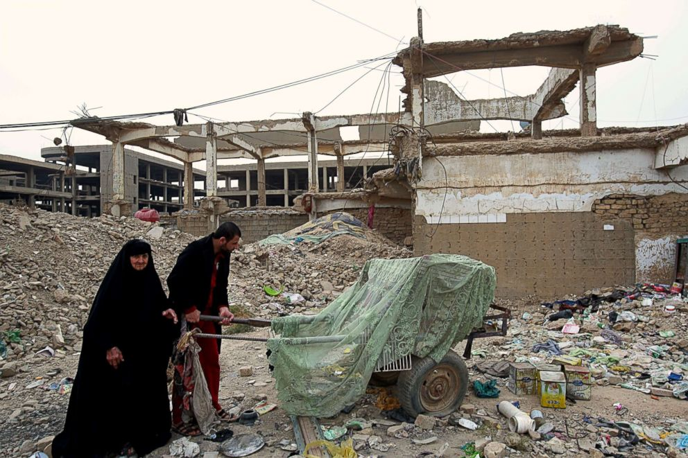 Homeless Iraqi people push their belongings through the rubble of al-Rashid military base belonging to the former Iraqi army in Baghdad, Iraq, Feb. 12, 2018. Kuwait this week is hosting a series of conferences on rebuilding Iraq after the onslaught of the Islamic State group.