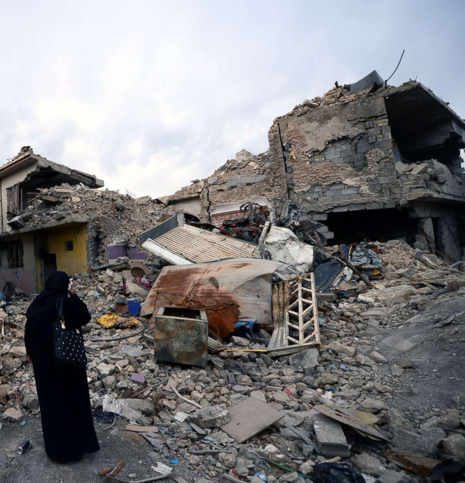 An Iraqi woman inspects the destruction in the old city district in the western part of Mosul city, Iraq, Feb. 3, 2018.