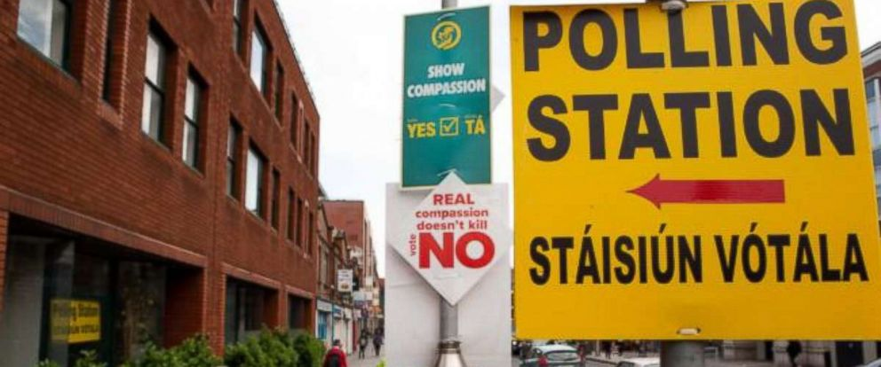 PHOTO: Pedestrians in Dublin walk past campaign posters calling on citizens to vote and a sign pointing the way to the nearby polling station on the final day of campaigning before the referendum on repealing the 8th Amendment, on May 21, 2018.