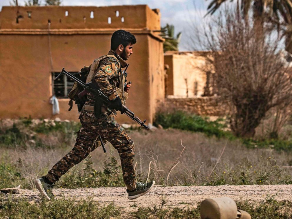 PHOTO: A member of the Syrian Democratic Forces (SDF) runs for cover during shelling on the Islamic State groups last holdout of Baghouz, in the eastern Syrian Deir Ezzor province, March 3, 2019.