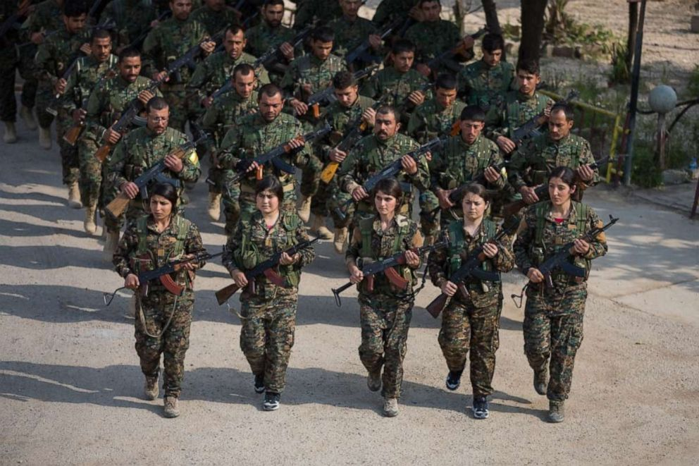 PHOTO: A Syrian Democratic Forces formation marches during a victory announcement ceremony over the defeat of Daeshs so-called physical caliphate Mar. 23, 2019 at Omar Academy, Deir ez-Zor, Syria.