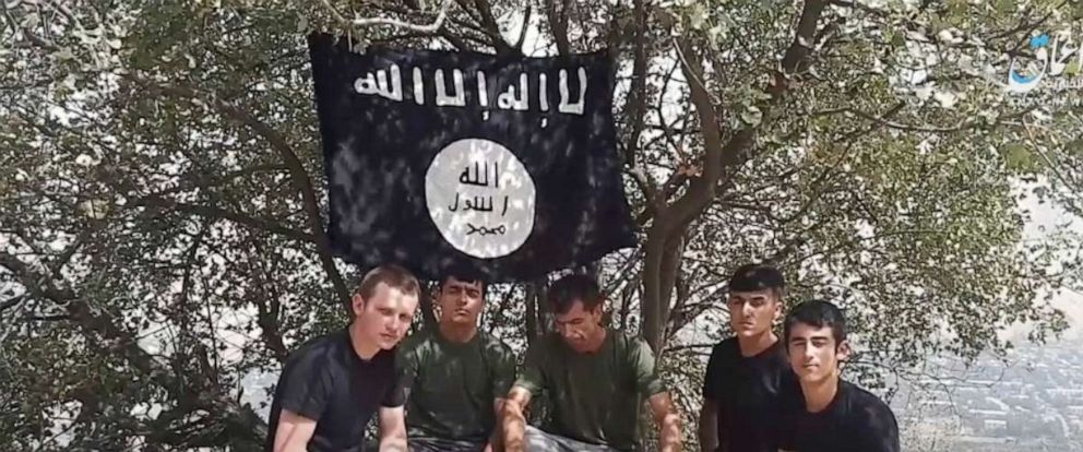 PHOTO: This grab taken from video, made available by Aamaq news agency of the Islamic State group, shows five men sitting on a hill against the backdrop of a black-and-white IS flag and declaring allegiance to IS leader Abu Bakr al-Baghdadi.