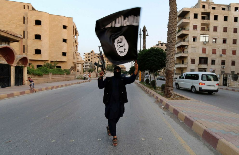 PHOTO: In this file photo, a member loyal to the Islamic State in Iraq and the Levant (ISIL) waves an ISIL flag in Raqqa, Syria, June 29, 2014.