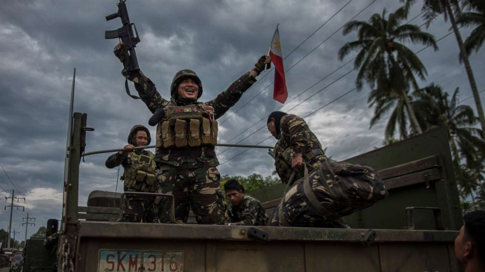 A government soldier waving the Philippine flag as they get ready to leave the battle against IS-inspired militants, Oct. 20, 2017, in Saguiaran town in Lanao del Sur, southern Philippines.