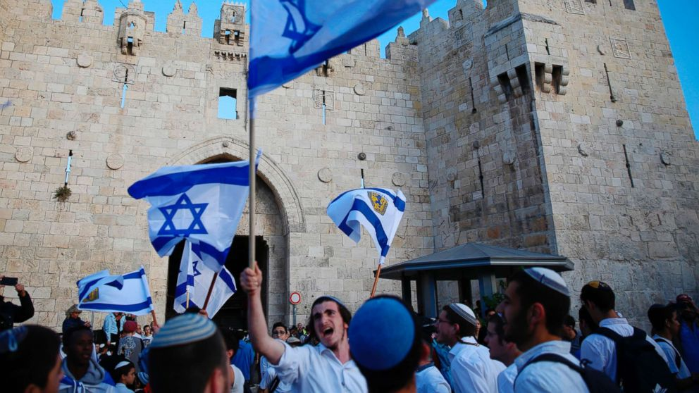 Israelis wave national flags outside the Old City's Damascus Gate, in Jerusalem, May 13, 2018. Israel's parliament has approved a controversial piece of legislation that defines the country as the nation-state of the Jewish people.