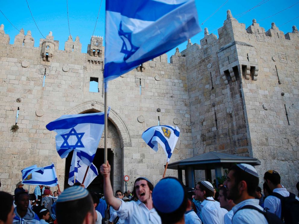 PHOTO: Israelis wave national flags outside the Old Citys Damascus Gate, in Jerusalem, May 13, 2018.