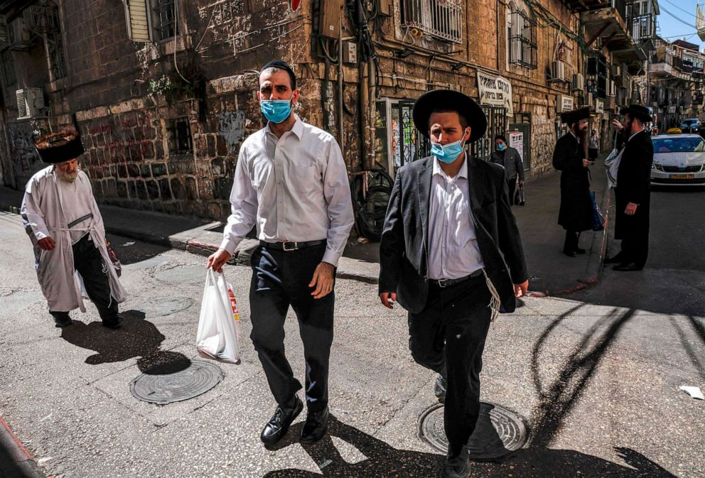 PHOTO: Ultra-Orthodox Jews, mask-clad due to the COVID-19 coronavirus pandemic, walk along a street in the neighborhood of Mea Shearim Jerusalem a few hours before the start of Yom Kippur, the Jewish holy day of Atonement, Sept. 27, 2020.