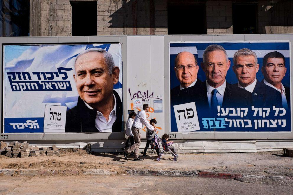People walk by election campaign billboards in Tel Aviv, Israel, April 3, 2019.