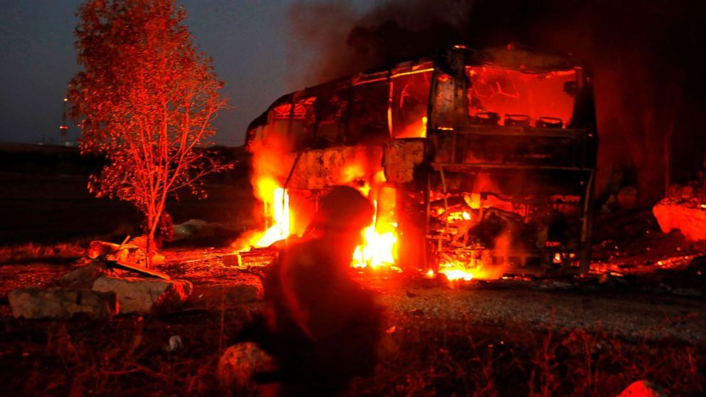 Israeli security forces and firefighters gather near a bus set ablaze after it was hit by a rocket fired from the Palestinian enclave, at the Israel-Gaza border near the kibbutz of Kfar Aza, on Nov. 12, 2018.