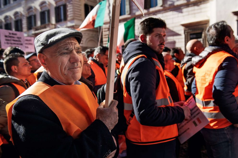 PHOTO: Men wearing orange vests march in an olive-growers protest in Rome, Feb. 14, 2018, to demand urgent measures in favor of olive oil producers impacted by hard frosts and Xylella, an olive tree disease.