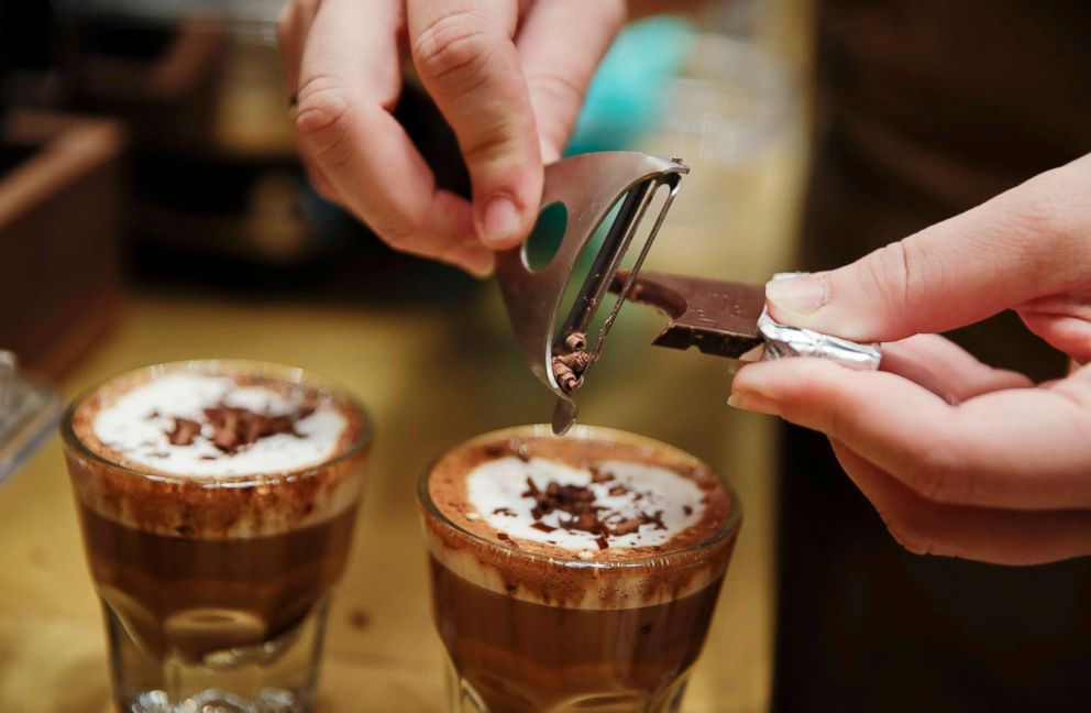 PHOTO: A waiter adds chocolate to coffee cups, at the Starbucks store in Milan, Sept. 4, 2018.