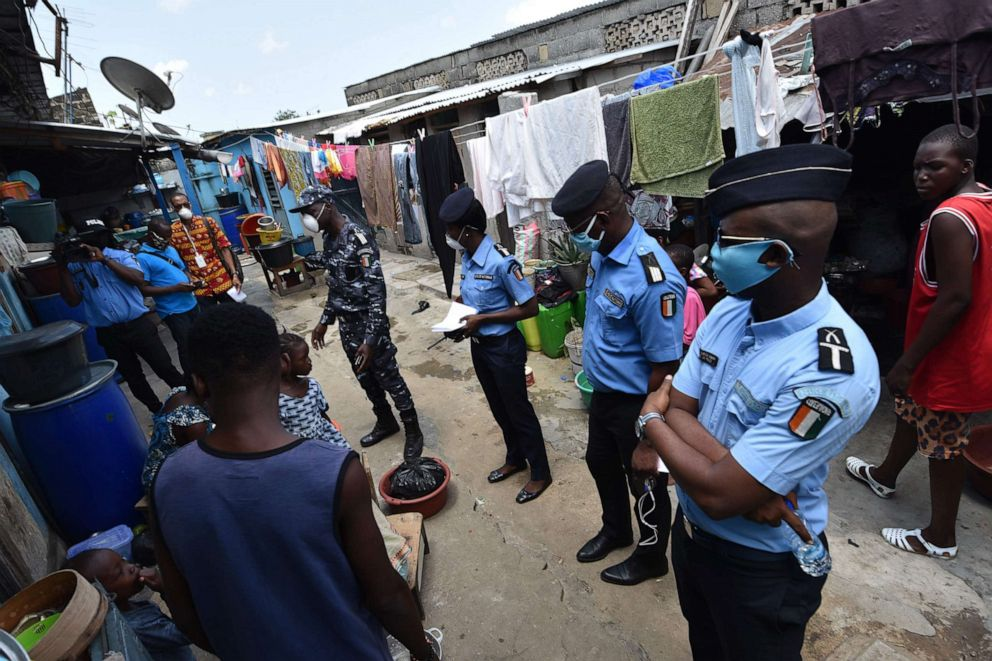 Residents listen on April 22, 2020, as Ivorian policemen talk about the use of protective masks against the spread of the COVID-19 coronavirus in the popular Attecoube district of Abidjan, Cote d'Ivoire.Sia Kambou/AFP via Getty Images
