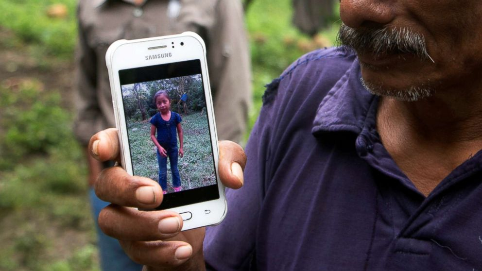 Domingo Caal, 61, grandfather of Jakelin, a 7-year-old girl who died in U.S. custody, holds his mobile phone with a picture of his granddaughter as he stands outside her house in Raxruha, Guatemala, Dec. 15, 2018.