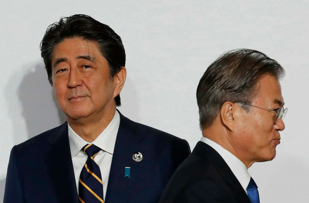 PHOTO: In this June 28, 2019, file photo, South Korean President Moon Jae-in, right, walks by Japanese Prime Minister Shinzo Abe upon his arrival for a welcome and family photo session at the G-20 leaders summit in Osaka, western Japan.