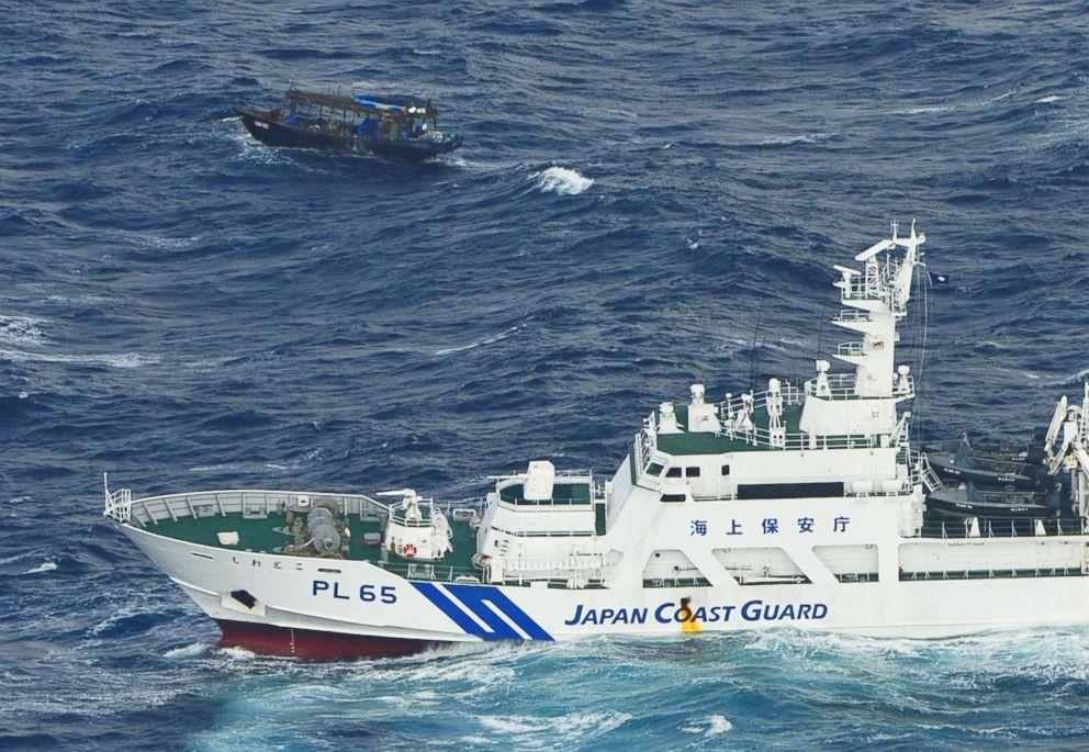 PHOTO: A wooden boat, top, is seen near a patrol ship of Japan Coast Guard off Matsumae, Hokkaido, Japan, Nov. 29, 2017.