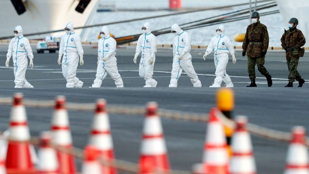Workers and army officers wearing protective suits walk away from the Diamond Princess cruise ship, as they prepare to transfer passengers tested positive for the novel coronavirus, at Daikoku Pier Cruise Terminal in Yokohama, south of Tokyo, Japan, Feb. 10, 2020.Workers and army officers wearing protective suits walk away from the Diamond Princess cruise ship, as they prepare to transfer passengers tested positive for the novel coronavirus, at Daikoku Pier Cruise Terminal in Yokohama, south of Tokyo, Japan, Feb. 10, 2020. Kim Kyung Hoon/Reuters