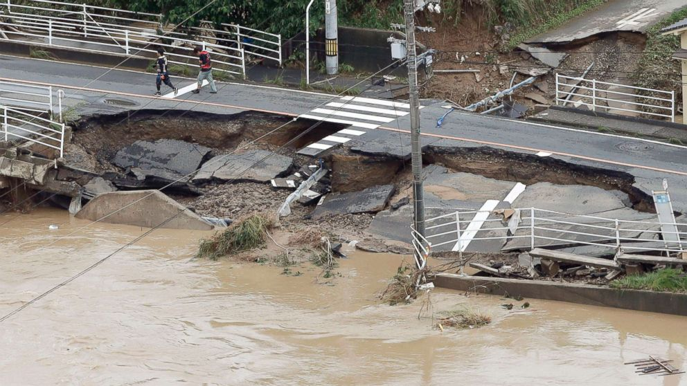 A road is damaged by flood water following heavy rain in Kurashiki city, Okayama prefecture, southwestern Japan, July 8, 2018.