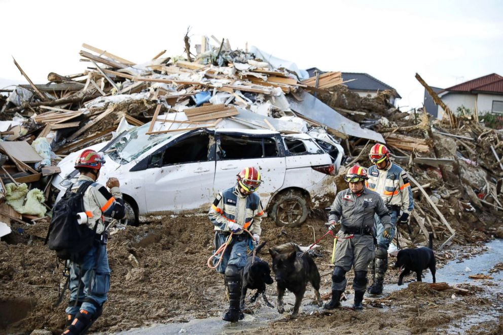 PHOTO: Firefighters with rescue dogs search for missing people after heavy rain hit southwestern Japan, in Kumano town, Hiroshima prefecture, July 9, 2018.